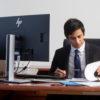 man sitting at a desk looking at notebook