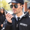 person in security jacket holding up a walkie talkie
