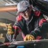 technician working under a car's hood